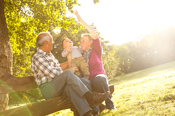 Grandparents and grandchild on bench 600x400
