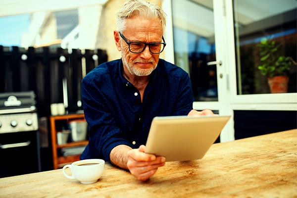 Older man in garden on ipad filter 600x400