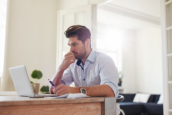 Young pensive man working at home 600x400px